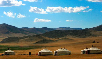 Mongolian nomads walk outside their traditional tent homes near Kharkorin.